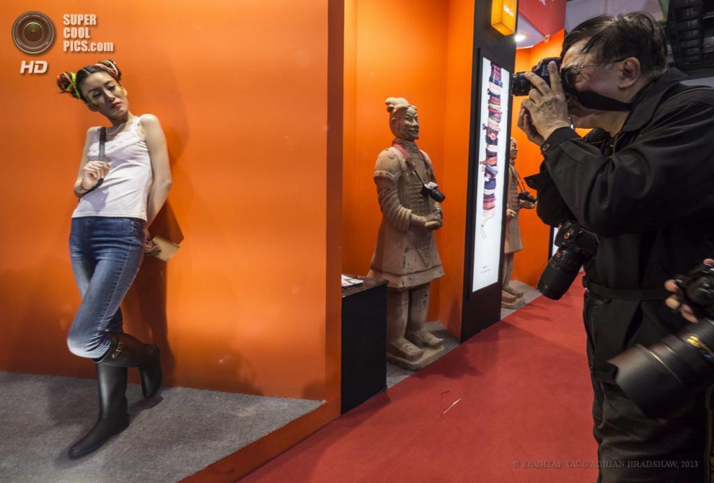 Китай. Пекин. 19 апреля. Типичная сцена для выставки фотографических технологий — мужчина фотографирует понравившуюся модель. (EPA/ИТАР-ТАСС/ADRIAN BRADSHAW)