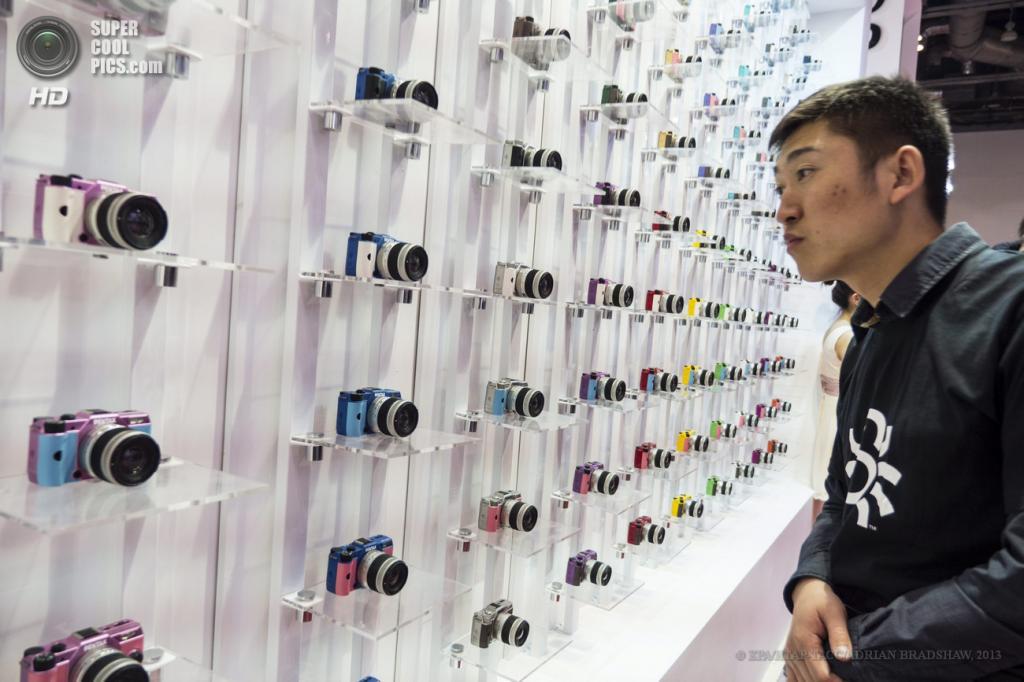 Китай. Пекин. 19 апреля. Посетитель рассматривает стенды с фотоаппаратами Pentax. (EPA/ИТАР-ТАСС/ADRIAN BRADSHAW)