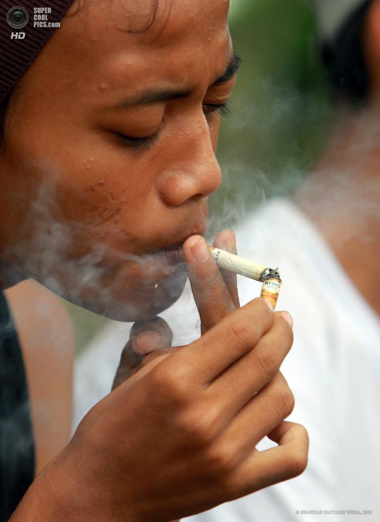 Индонезия. Богор, Западная Ява. 30 мая. Несовершеннолетний школьник курит после уроков. (EPA/ИТАР-ТАСС/ADI WEDA)