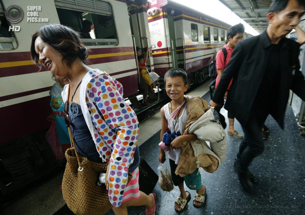 Таиланд. Бангкок. 28 мая. Мама с сыном бегут по платформе на главном железнодорожном вокзале. (EPA/ИТАР-ТАСС/NARONG SANGNAK)