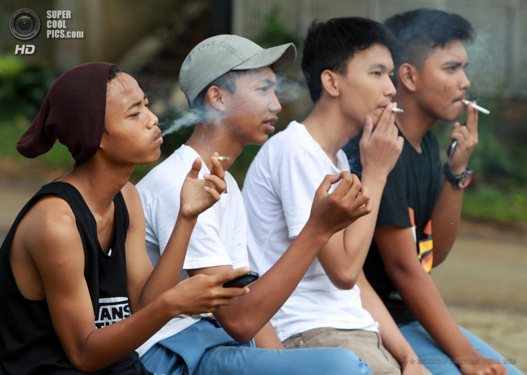 Индонезия. Богор, Западная Ява. 30 мая. Несовершеннолетние школьники курят после уроков. (EPA/ИТАР-ТАСС/ADI WEDA)