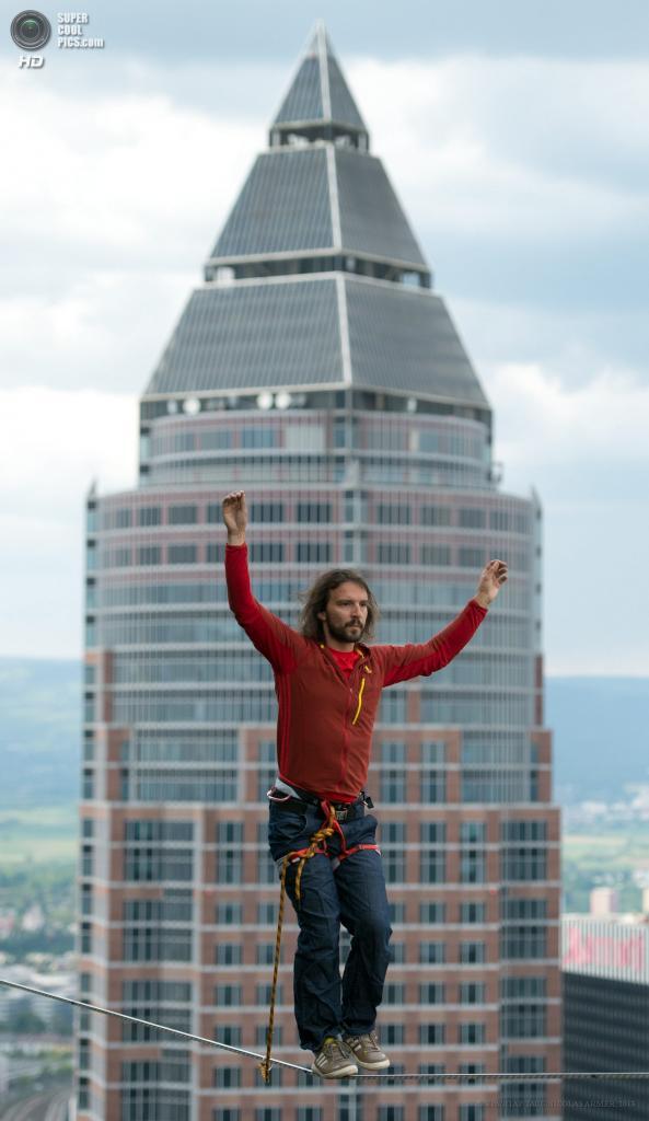 Германия. Франкфурт-на-Майне, Гессен. 25 мая. Австрийский канатоходец Райнхард Кляйндль проходит на канате меж двух башен Tower 185 во время Фестиваля небоскребов. (EPA/ИТАР-ТАСС/NICOLAS ARMER)