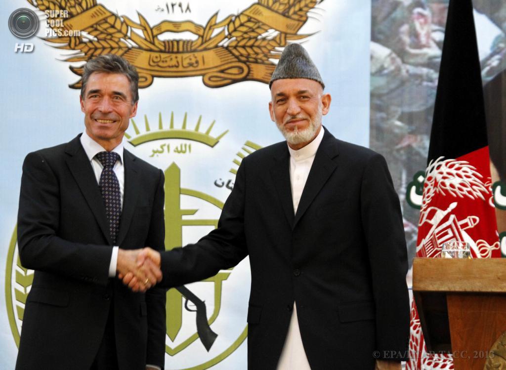 Афганистан. Кабул. 18 июня. Президент Афганистана Хамид Карзай (справа) пожимает руку генеральному секретарю НАТО Андерсу Фогу Расмуссену во время церемонии передачи силами НАТО полной ответственности за обеспечение безопасности в стране властям Афганистана. (EPA/ИТАР-ТАСС/S. SABAWOON)