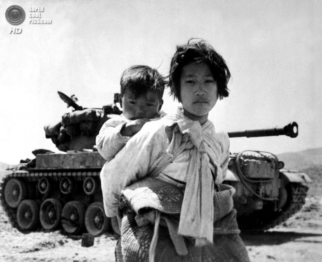 Корея. Коян. 9 июня 1951 года. Корейская девочка с младшим братом на спине устало тащится мимо танка M26 Pershing. (U.S. Army Korea)