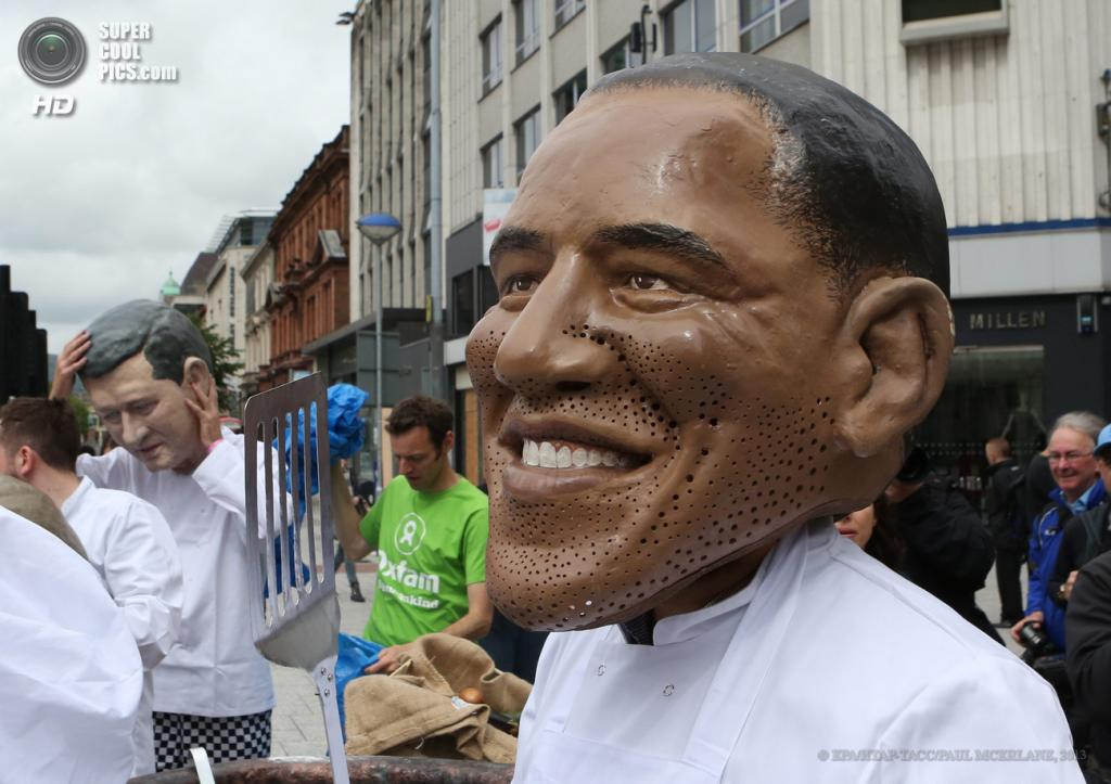 Великобритания. Белфаст, Северная Ирландия. 16 июня. Член движения Enough Food For Everyone IF варит «мировой суп» в маске президента США Барака Обамы накануне саммита «Большой восьмёрки». (EPA/ИТАР-ТАСС/PAUL MCERLANE)