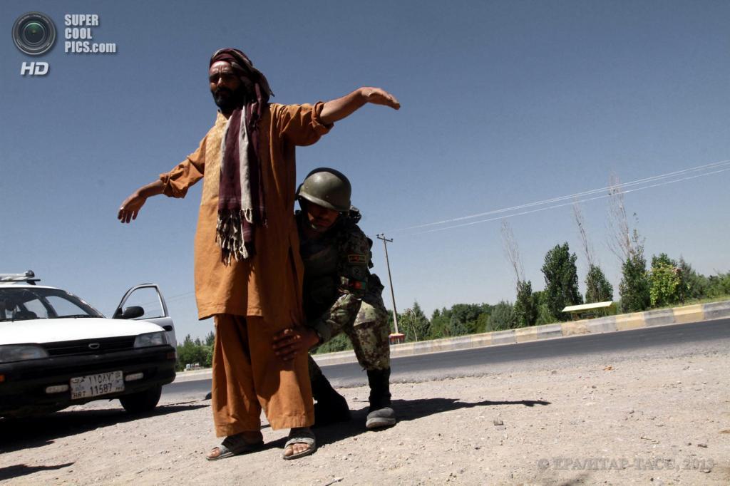 Афганистан. Герат. 18 июня. Афганский солдат обыскивает мужчину на контрольно-пропускном пункте. (EPA/ИТАР-ТАСС/JALIL REZAYEE)