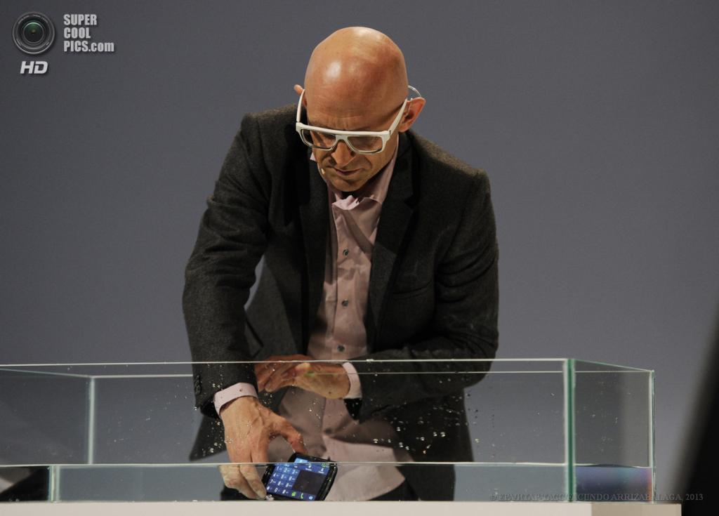 Великобритания. Лондон. 20 июня. Промоутер демонстрирует водостойкость нового защищённого смартфона Samsung Galaxy S4 Active в выставочном центре «Эрлс Корт». (EPA/ИТАР-ТАСС/FACUNDO ARRIZABALAGA)