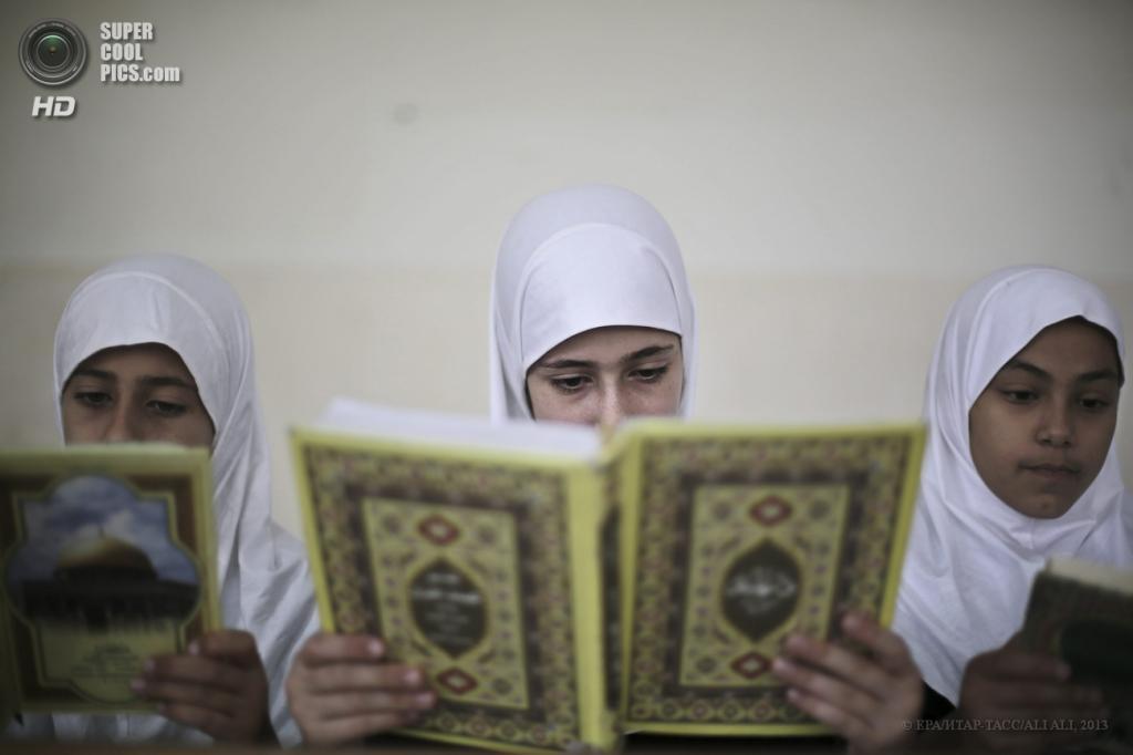 Палестина. Сектор Газа. 3 июня. Палестинские девочки читают Коран в летнем лагере. (EPA/ИТАР-ТАСС/ALI ALI)