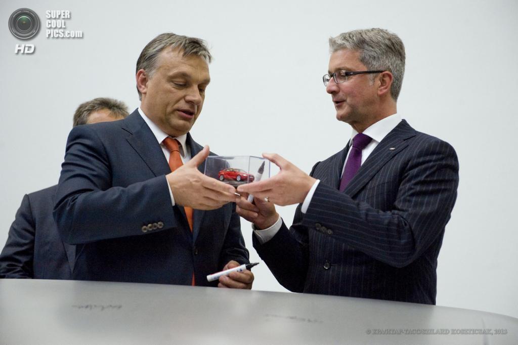 Венгрия. Дьёр. 12 июня. Председатель правления Audi AG Руперт Штадлер (справа) вручает премьер-министру Венгрии Виктору Орбану игрушечный автомобиль. (EPA/ИТАР-ТАСС/SZILARD KOSZTICSAK)