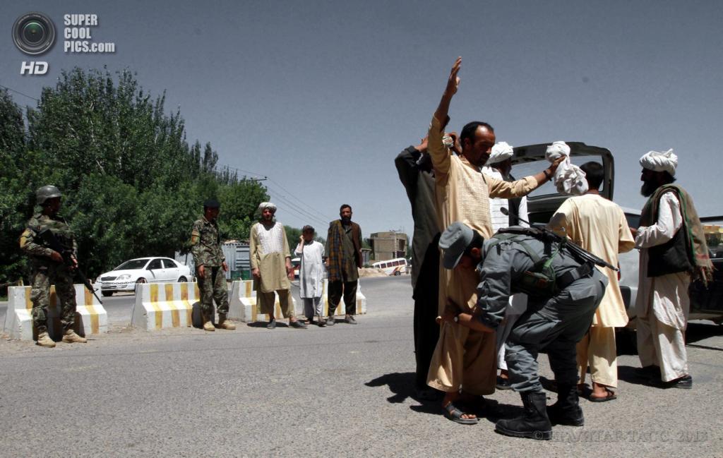 Афганистан. Герат. 18 июня. Афганские солдаты обыскивают людей на контрольно-пропускном пункте. (EPA/ИТАР-ТАСС/JALIL REZAYEE)