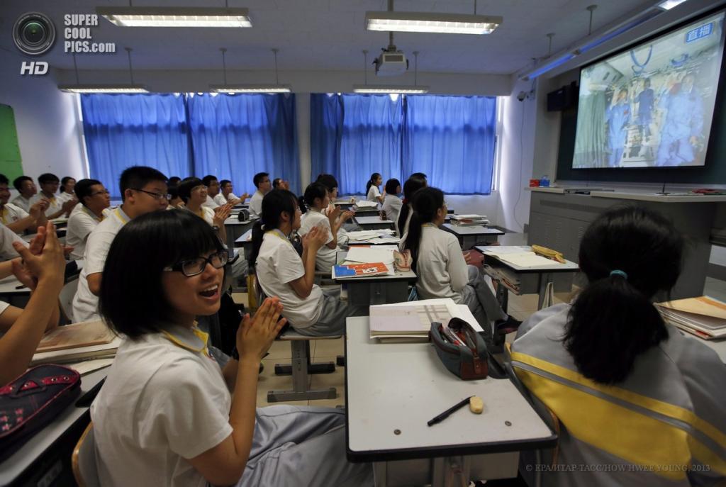 Китай. Пекин. 19 июня. Китайские астронавты на орбитальном модуле «Тяньгун-1» проводят урок физики для школьников и студентов в прямом эфире. (EPA/ИТАР-ТАСС/HOW HWEE YOUNG)