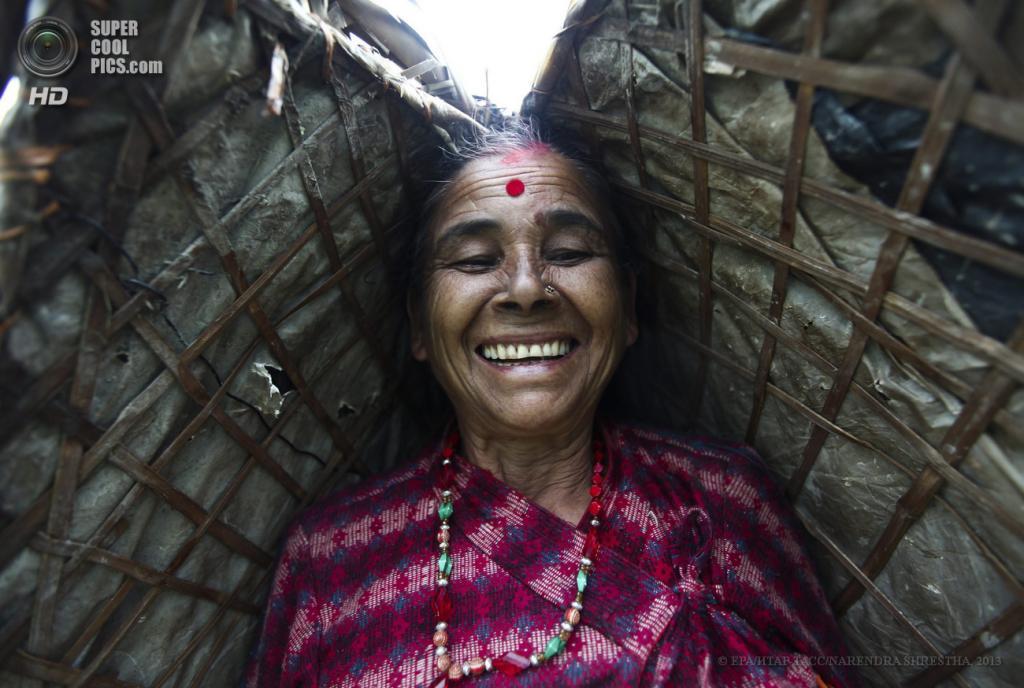 Непал. Катманду. 26 июня. Женщина направляется к своему участку поля, укрываясь от дождя национальным зонтом Ghoom. (EPA/ИТАР-ТАСС/NARENDRA SHRESTHA)
