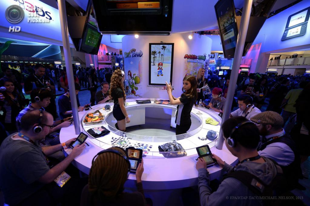 США. Лос-Анджелес, Калифорния. 11 июня. Посетители принимают участие в соревновании у стенда Nintendo 3DS на выставке E3 2013. (EPA/ИТАР-ТАСС/MICHAEL NELSON)