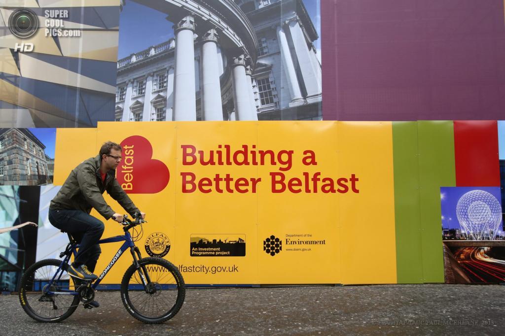 Великобритания. Белфаст, Северная Ирландия. 15 июня. Велосипедист проезжает мимо огромных принтов, скрывающих нелицеприятные фасады, накануне саммита «Большой восьмёрки». (EPA/ИТАР-ТАСС/PAUL MCERLANE)