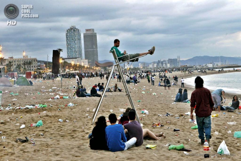 Испания. Барселона, Каталония. 24 июня. Подростки отдыхают на пляже после празднования Костров святого Иоанна Крестителя. (EPA/ИТАР-ТАСС/ALBERT OLIVE)