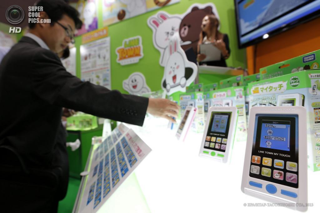 Япония. Токио. 13 июня. Посетитель рассматривает смартфоноподобную игрушку «Line Town My Touch» от Tomy на выставке Tokyo Toy Show 2013. Устройство предназначено для обучения детей. (EPA/ИТАР-ТАСС/KIYOSHI OTA)