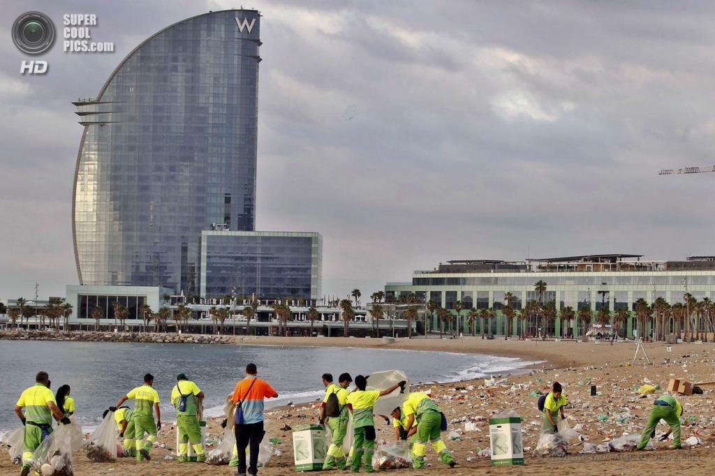 Испания. Барселона, Каталония. 24 июня. Работники городских служб собирают мусор на пляже после празднования Костров святого Иоанна Крестителя. (EPA/ИТАР-ТАСС/ALBERT OLIVE)