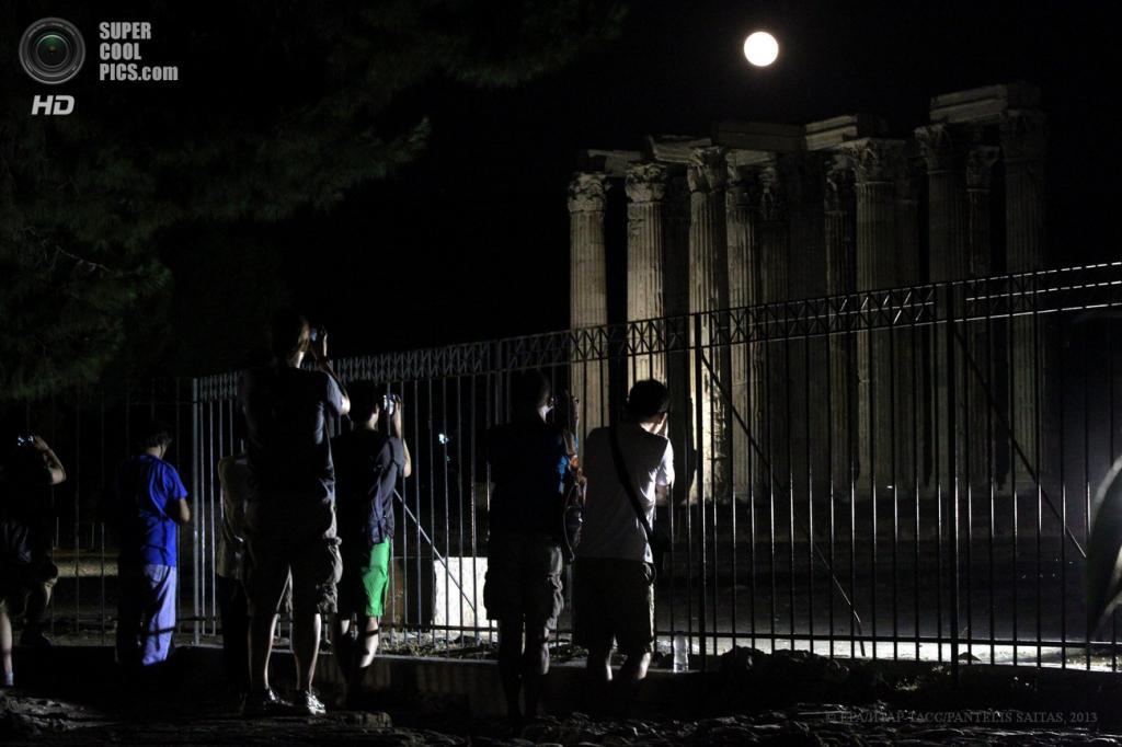 Греция. Афины. 23 июня. Туристы фотографируют Олимпейон — храм Зевса Олимпийского — на фоне суперлуния. (EPA/ИТАР-ТАСС/PANTELIS SAITAS)