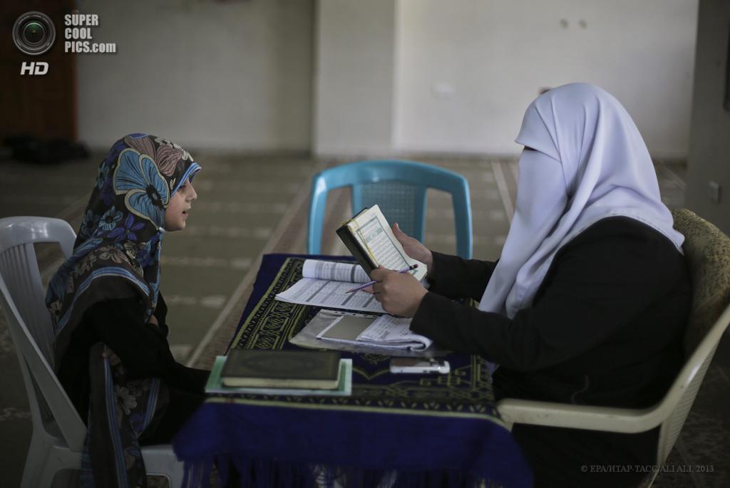 Палестина. Сектор Газа. 3 июня. Палестинская девочка с учительницей читают Коран в летнем лагере. (EPA/ИТАР-ТАСС/ALI ALI)