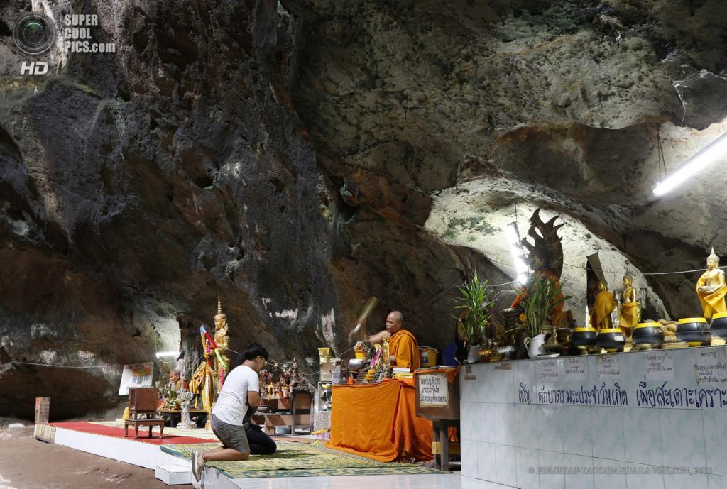 Таиланд. Ратчабури. 4 июня. Буддийский монах благословляет паломников внутри пещеры Chompol. (EPA/ИТАР-ТАСС/BARBARA WALTON)