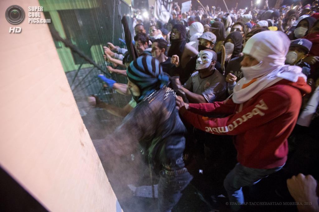 Бразилия. Сан-Паулу. 17 июня. Участники акции протеста против повышения стоимости проезда в общественном транспорте штурмуют здание правительства. (EPA/ИТАР-ТАСС/SEBASTIAO MOREIRA)