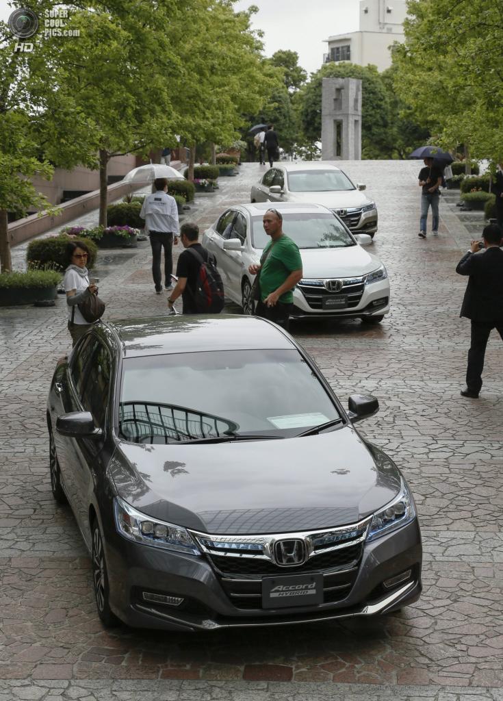 Япония. Токио. 20 июня. Пешеходы рассматривают припаркованные новые гибридные седаны Honda Accord Hybrid. (EPA/ИТАР-ТАСС/KIMIMASA MAYAMA)