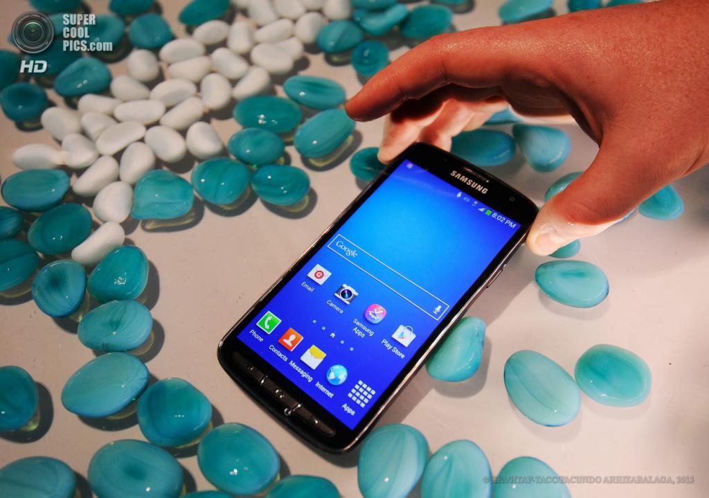 Великобритания. Лондон. 20 июня. Посетители рассматривают лежащий в воде защищённый смартфон Samsung Galaxy S4 Active во время презентации новых гаджетов Samsung в выставочном центре «Эрлс Корт». (EPA/ИТАР-ТАСС/FACUNDO ARRIZABALAGA)