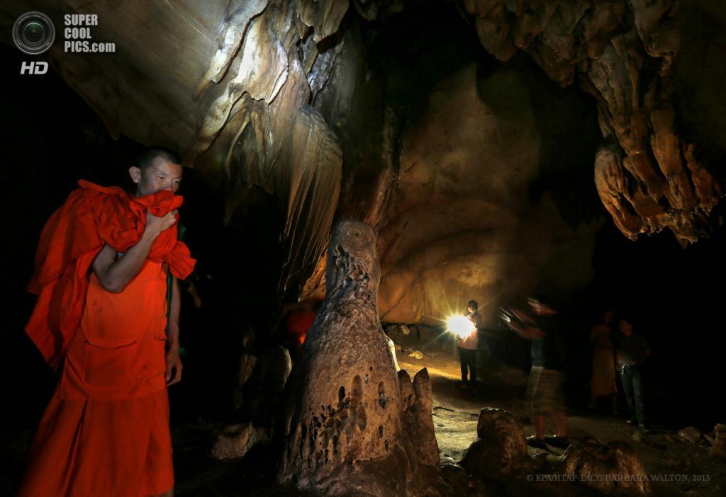 Таиланд. Чиангмай. 14 мая. Проводник подсвечивает стены для туристов, пока буддийский монах проходит мимо сталагмита внутри пещеры Chiang Dao. (EPA/ИТАР-ТАСС/BARBARA WALTON)