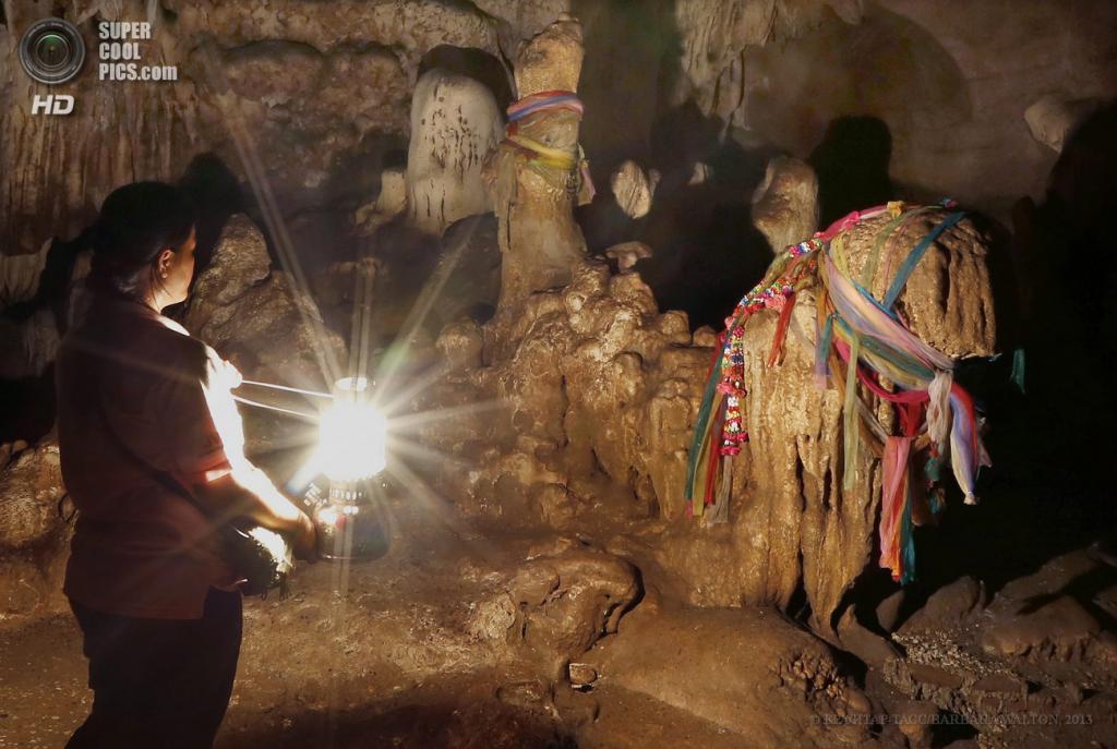 Таиланд. Чиангмай. 14 мая. Проводник с керосиновой лампой освещает образование из известняка и кальцита, которое напоминает лошадь, обмотанную цветным сукном на хвосте и голове внутри пещеры Tham Ma. (EPA/ИТАР-ТАСС/BARBARA WALTON)