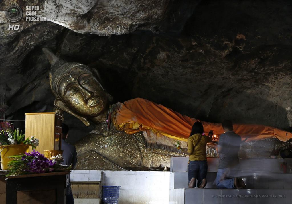 Таиланд. Ратчабури. 4 июня. Буддисты молятся на коленях перед огромной статуей Будды внутри пещеры Chompol. (EPA/ИТАР-ТАСС/BARBARA WALTON)