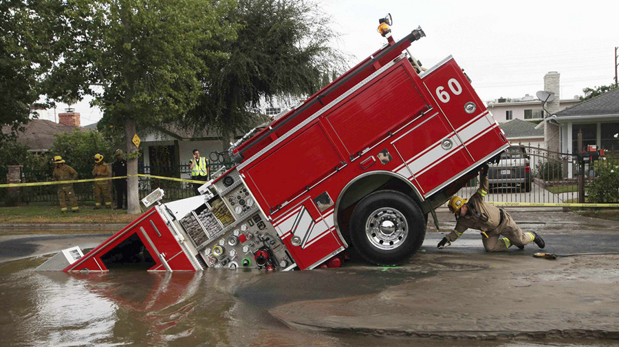 США. Лос-Анджелес, Калифорния. 8 сентября 2009 года. Пожарный автомобиль, попавший в карстовую воронку посреди дороги. (AP Photo/Nick Ut)