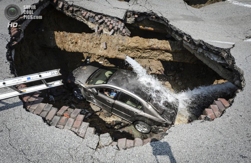 США. Толедо, Огайо. 3 июля 2013 года. Автомобиль 60-летней Памелы Нокс, попавший в карстовую воронку посреди дороги из-за прорыва водопроводной магистрали. (AP Photo/Lt. Matthew Hertzfeld, Toledo Fire and Rescue)