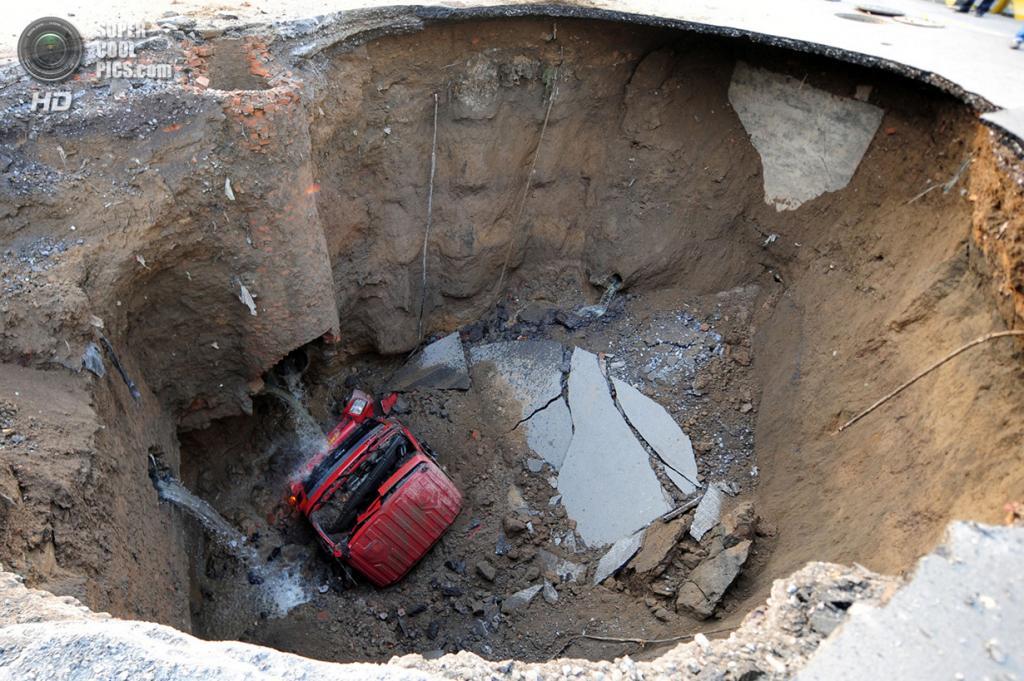 Китай. Пекин. 26 апреля 2011 года. Грузовик в плену карстовой воронки. Водитель и пассажир успели выскочить из салона до того, как автомобиль рухнул в провал. (AFP/Getty Images)