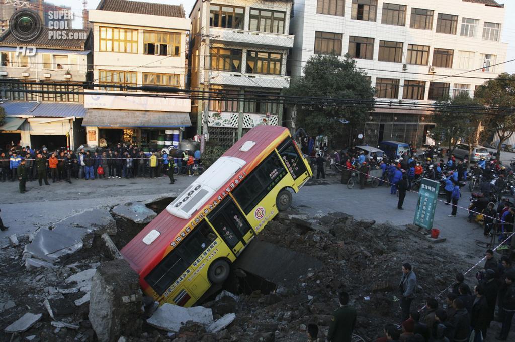 Китай. Руйань, Чжэцзян. 16 января 2011 года. Автобус после падения в карстовую воронку, образованную подземным взрывом. (REUTERS/China Daily)