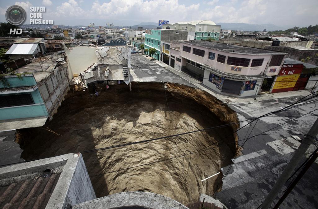 Гватемала. Гватемала. 1 июня 2010 года. Последствия урагана Агата — гигантская карстовая воронка на перекрестке. (REUTERS/Daniel LeClair)
