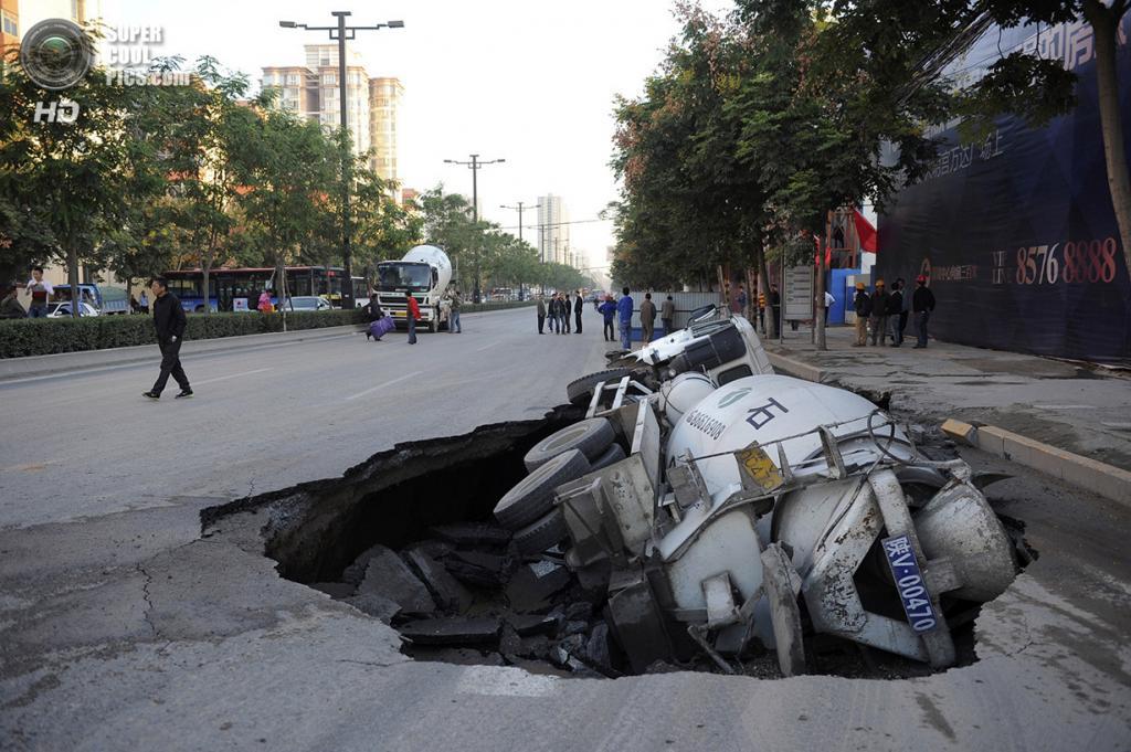 Китай. Сиань, Шэньси. 28 сентября 2012 года. Автобетоносмеситель, завалившийся на бок в карстовую воронку. (REUTERS/China Daily)