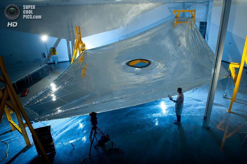 США. Хантсвилл, Алабама. Полномасштабная солнцезащитная мембрана телескопа «Джеймс Уэбб» во время испытаний. Телескоп будет сочетать пять таких мембран и все они должны быть расположены с точностью до миллиметра. (Northrop Grumman Aerospace Systems)