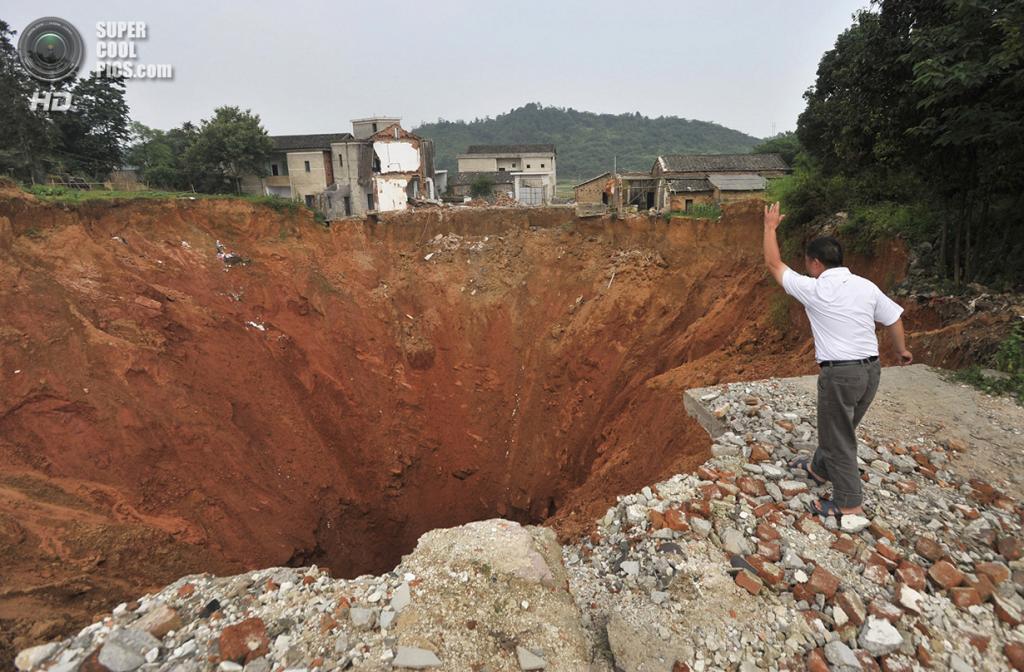 Китай. Дачэнцяо, Хунань. 15 июня 2010 года. Мужчина бросает камень в карстовую воронку, образованную близ средней школы. (REUTERS/Stringer)