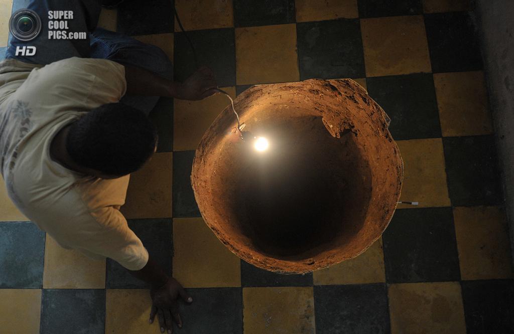 Гватемала. Гватемала. 19 июля 2011 года. Мужчина инспектирует небольшую карстовую воронку, образовавшуюся прямо под домом. (JOHAN ORDONEZ/AFP/Getty Images)