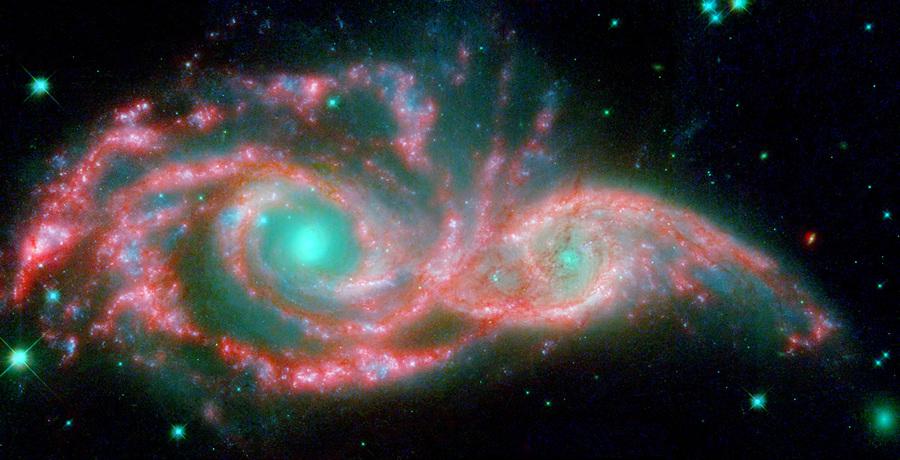 Взаимодействующие галактики NGC 2207 и IC 2163. (NASA/JPL-Caltech/STScI/Vassar)