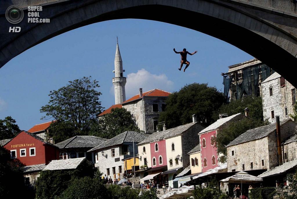 Босния и Герцеговина. Мостар, Герцеговино-Неретвенский кантон. Мужчина прыгает со Старого моста, где соревнования по прыжкам воду устраивались ещё 447 лет назад. (REUTERS/Dado Ruvic)
