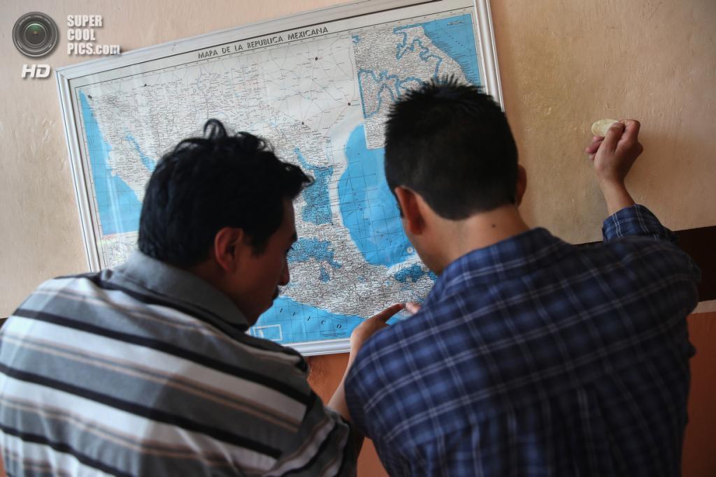Мексика. Арриага, Чьяпас. 3 августа. Иммигранты рассматривают карту Мексики перед посадкой на грузовой поезд. (John Moore/Getty Images)
