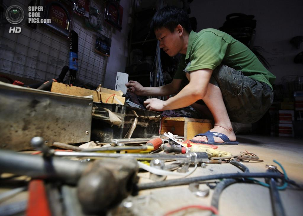 Китай. Пекин. 8 августа. Изобретатель Тао Сянли работает над усовершенствованием своего самодельного робота, претенциозно названного «Король инноваций». (REUTERS/Kim Kyung-Hoon)