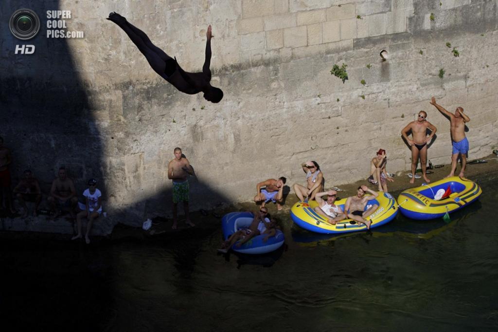 Босния и Герцеговина. Мостар, Герцеговино-Неретвенский кантон. Зрители наблюдают за очередным прыжком спортсмена со Старого моста. (AP Photo/Amel Emric)