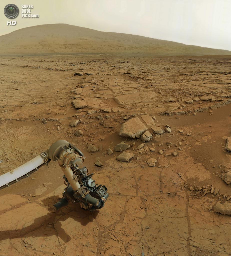 Марс. 3 февраля. «Кьюриосити» проводит бурение грунта; на заднем плане — гора Шарпа. (NASA/JPL-Caltech/Olivier de Goursac)