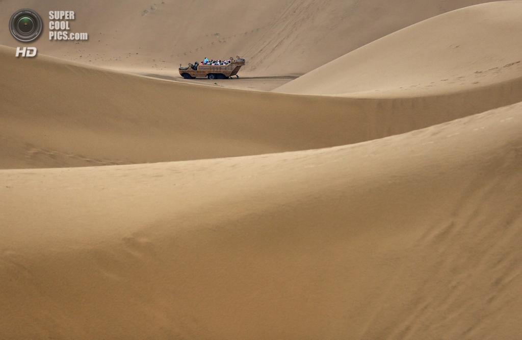 Китай. Ордос, Внутренняя Монголия. 18 июля. Туристы путешествуют по дюнам. (Feng Li/Getty Images)