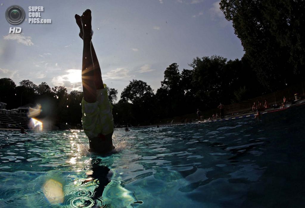 Австрия. Вена. Мальчик ныряет в бассейн, чтобы охладиться во время жары. (REUTERS/Leonhard Foeger)