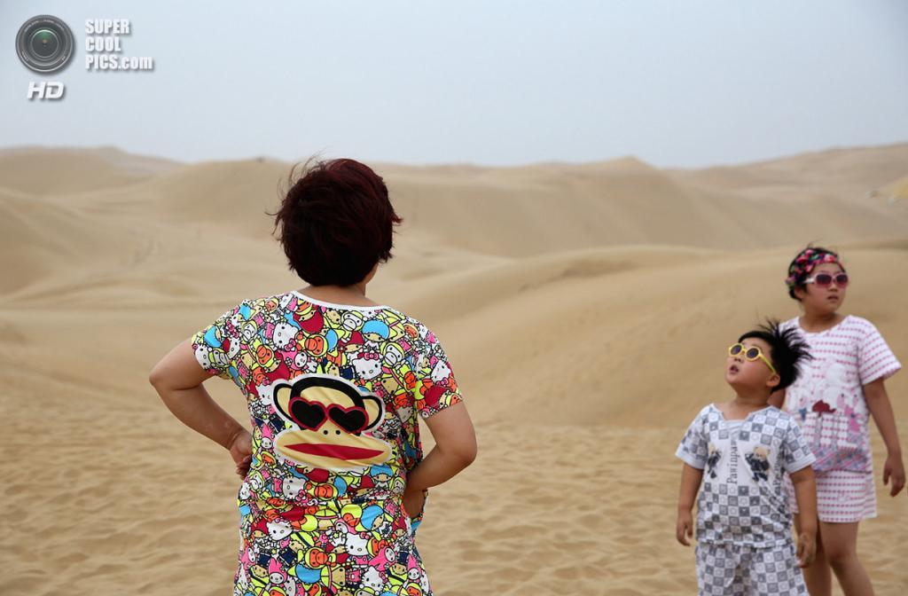 Китай. Ордос, Внутренняя Монголия. 21 июля. Туристы наслаждаются красотой пустыни. (Feng Li/Getty Images)