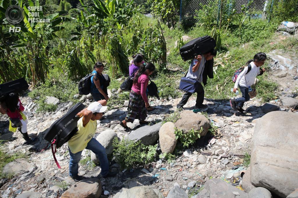 Мексика. Талисман, Чьяпас. 1 августа. Группа гватемальских нелегальных иммигрантов с багажом идут по направлению к железной дороге. (John Moore/Getty Images)