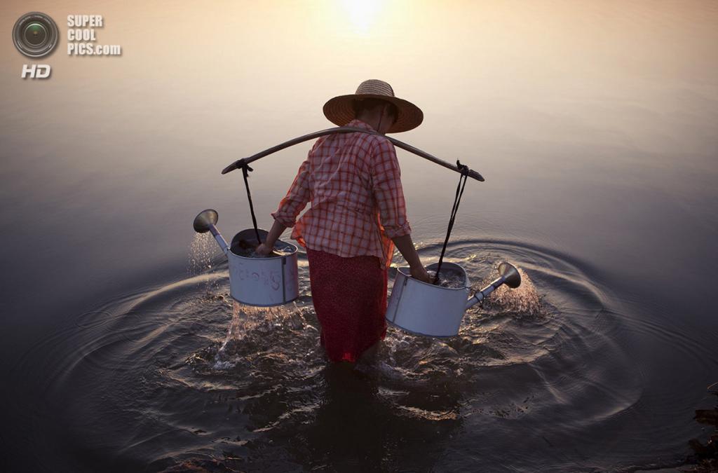 Достойный победы: Женщина в воде. «Женщина набирает воду из реки у деревни Баган, Мьянма». (Marcelo Salvador/National Geographic Traveler Photo Contest)